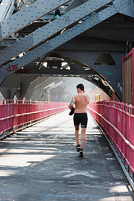 Man running on bridge - p312m1192853 by Karl Forsberg