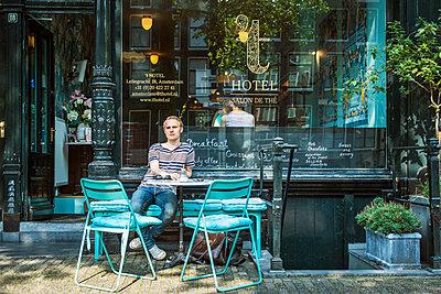 Netherlands, Amsterdam, Man sitting outside cafe - p352m1099979f by Johan Mård