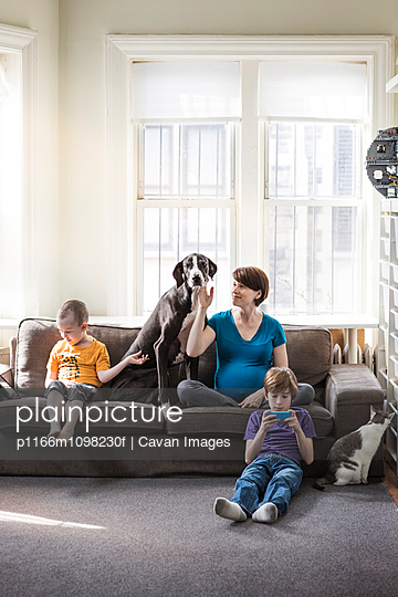Family relaxing at home - p1166m1098230f by Cavan Images