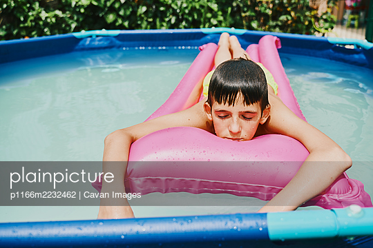 Front view of a blonde boy lying on a pink float resting in a pool. - p1166m2232462 by Cavan Images
