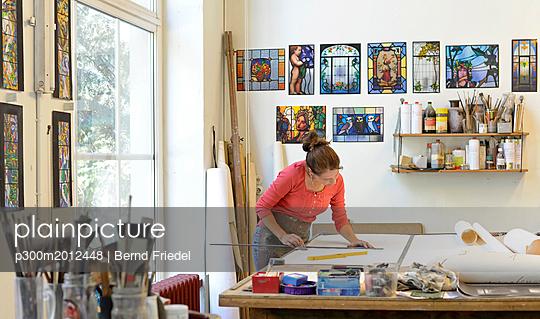 Woman working on draft in glazier's workshop - p300m2012448 von Bernd Friedel