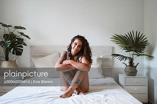 Smiling young woman hugging knees while sitting on bed against wall at home - p300m2206612 by Eva Blanco