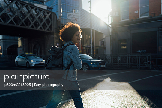 Afro young woman with backpack crossing street in city - p300m2213905 by Boy photography