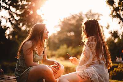 Happy girlfriends sitting in park during summer at sunset - p1166m2212482 by Cavan Images