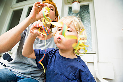Toddler with mother on balcony blowing streamer - p300m1494743 by Stefanie Päffgen
