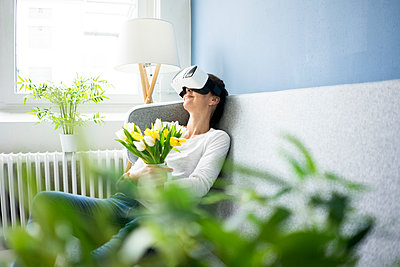 Smiling woman sitting on couch wearing VR glasses holding bunch of tulips - p300m1563357 by Robijn Page