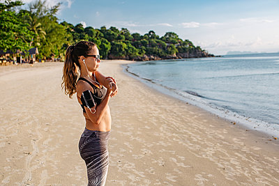 Thailand, Koh Phangan, Sportive woman doing workout on the beach - p300m2005454 by Mosuno Media