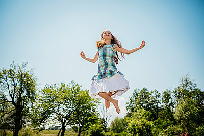 Carefree girl in dress jumping for joy in sunny backyard - p301m2075901 by Sven Hagolani