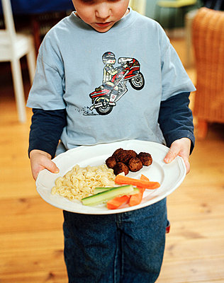 Boy holding meatballs and vegetables in plate - p31225730 by Per Eriksson