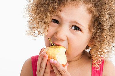 Mixed race girl eating apple - p555m1479691 by John Fedele