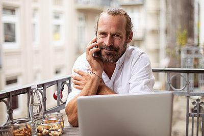Mann telefoniert mit Smartphone auf dem Balkon - p788m1424669 von Lisa Krechting