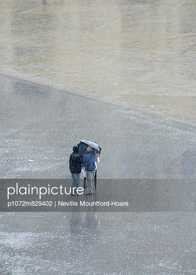 People in distance caught in heavy rain storm - p1072m829402 by Neville Mountford-Hoare