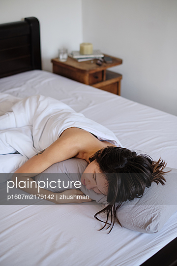 Young woman sleeping in her bed - p1607m2179142 by zhushman