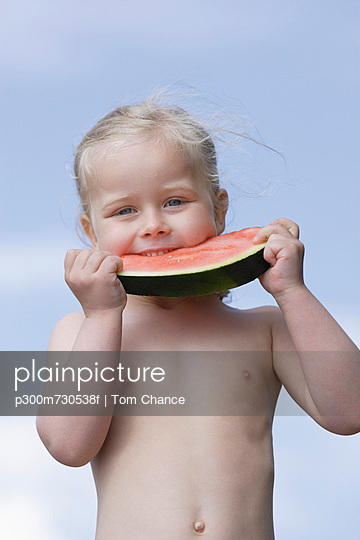 Girl eating piece of watermelon - p300m730538f by Tom Chance