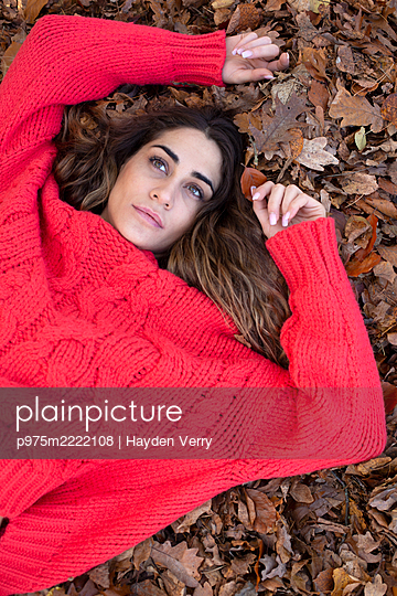 Young woman in red jumper on autumn leaves - p975m2222108 by Hayden Verry
