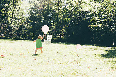 Toddler in garden playing with balloon - p1086m1154439 by Carrie Marie Burr