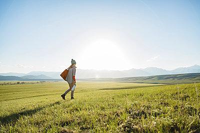 Rear view of female hiker walking on grassy field against clear sky - p1166m1489442 by Cavan Images