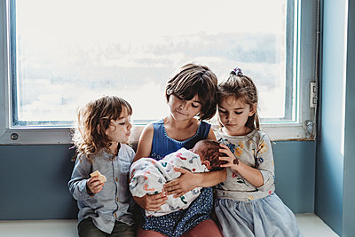Front view of three siblings holding newborn brother against window - p1166m2162543 by Cavan Images