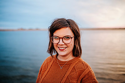 Center Portrait of a woman wearing glasses near a lake - p1166m2208509 by Cavan Images