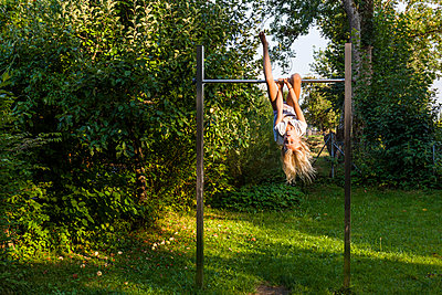 Girl exercising on gymnastics bar in garden - p300m2030354 by Tom Chance