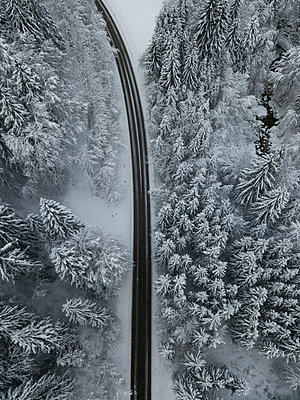 Aerial view of empty asphalt road cutting through snow-covered forest in Achtal - p300m2206845 by Matthias Aletsee