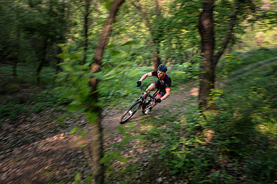 Man riding mountain bike in nature in the Bologna countryside, Italy - p307m937556f by Enrico Calderoni