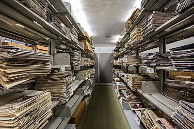Zeitungen in Regalen in einer Bibliothek - p397m1515454 von Peter Glass