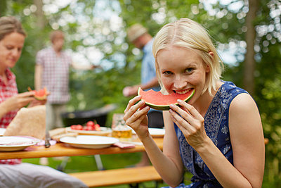 Woman eating watermelon outdoors - p429m713146 by Stephen Lux