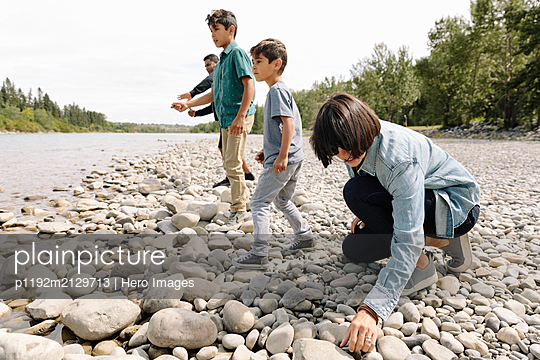 Family throwing pebbles on riverbank - p1192m2129713 by Hero Images