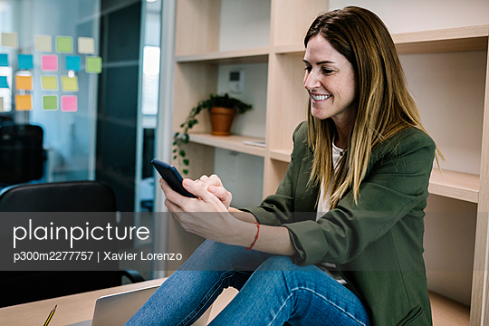 Smiling female entrepreneur using smart phone while sitting on desk at office - p300m2277757 by Xavier Lorenzo