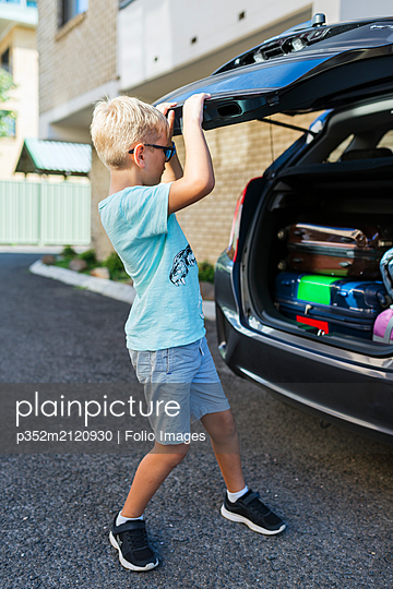Boy closing car boot - p352m2120930 by Folio Images