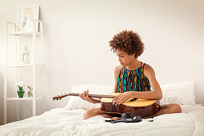 Girl playing guitar while sitting on bed at home - p1166m1099032f by Cavan Images