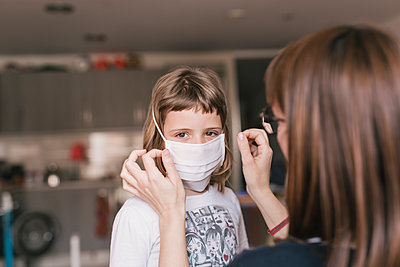 Mother putting medical mask on her daughter to protect himself from the coronavirus - p1166m2182921 by Cavan Images