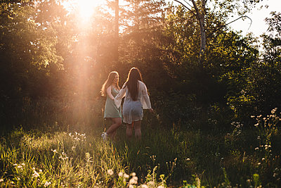 Two happy girlfriends walking in forest during summer - p1166m2212458 by Cavan Images