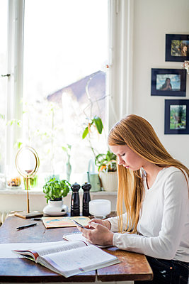 Side view of girl using smart phone while sitting with books at home - p426m1517748 by Maskot