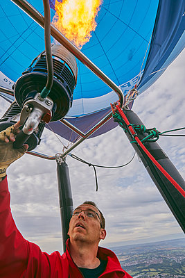 A balloon pilot adjusting the burning gas jets that heat air inside the balloon, during the Bristol International Balloon Fiesta, England, United Kingdom, Europe - p871m2152464 by Nigel Hicks