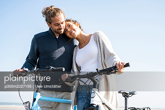 Beautiful woman with head on boyfriend's shoulder standing with bicycles at beach against clear sky on sunny day - p300m2227195 by Uwe Umstätter