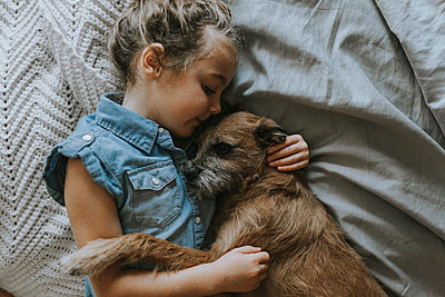 High angle view of girl sleeping with schnauzer on bed - p1166m1203765 by Cavan Images