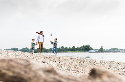 Happy father with two sons and football walking at the riverside - p300m2005344 by Uwe Umstätter