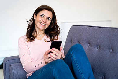 Smiling woman holding mobile phone while sitting on sofa at home - p300m2266131 by Giorgio Fochesato