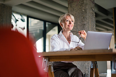 Smiling businesswoman with laptop holding eyeglasses while sitting at desk in home office - p300m2266959 by Robijn Page