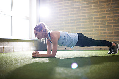 Woman doing plank in gym - p429m2019259 by Peter Muller