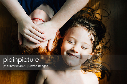 High angle view of cute smiling siblings lying on hardwood floor at home - p1166m2034891 by Cavan Images