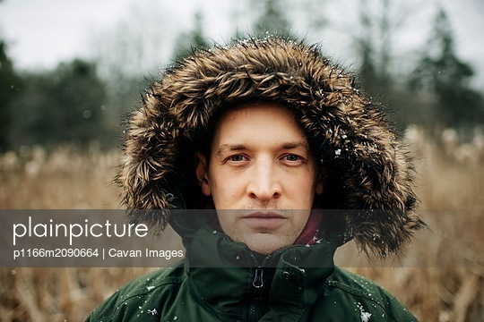 portrait ofman in his 30's with hood up standing in the snow in winter - p1166m2090664 by Cavan Images
