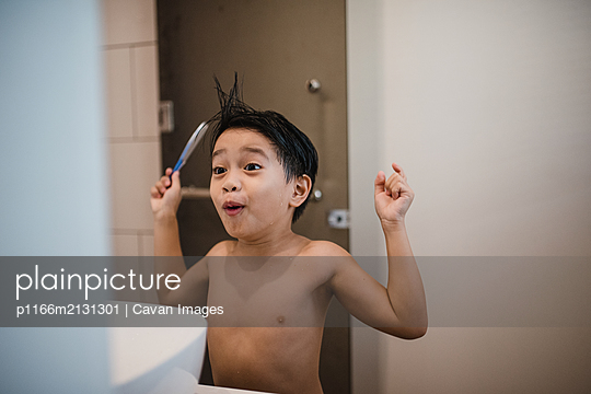 Asian boy combing hair in front of mirror - p1166m2131301 by Cavan Images