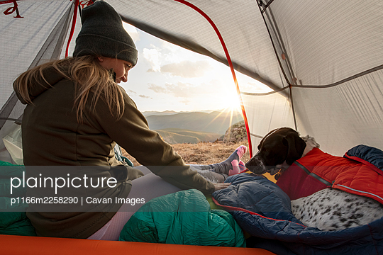 Woman camping with dog in tent on mountain during vacation - p1166m2258290 by Cavan Images