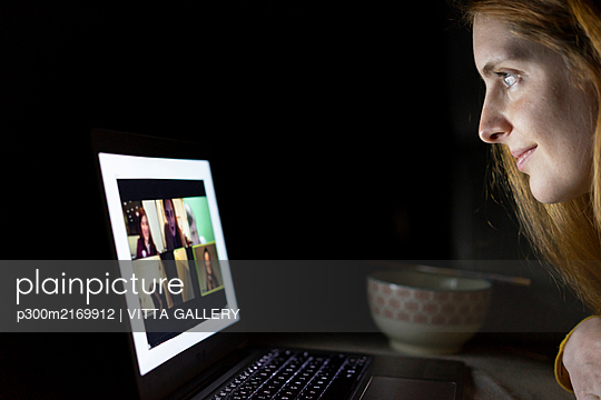 Young woman having a laptop video conference on the couch at home - p300m2169912 by VITTA GALLERY