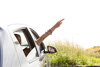 Woman waving hand through window while traveling in car against clear sky during sunny day - p1166m2035051 by Cavan Images