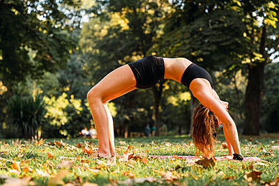 Fit young woman practicing yoga in a park - p300m2058939 von Kike Arnaiz