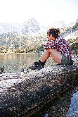 Austria, Tyrol, woman sitting on tree trunk at lake Seebensee - p300m2083378 by Florian Küttler